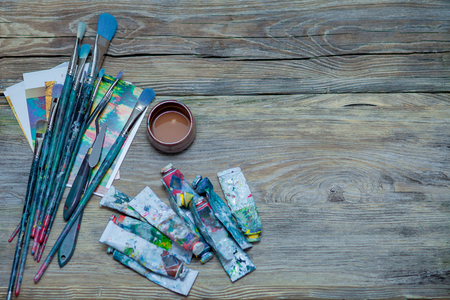 The tools of the artist - paints and brushes on wooden background