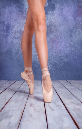 elegant girl: The close-up feet of  young ballerina in pointe shoes against the background of the wooden floor