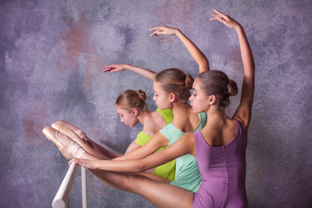 flexable: Three young ballerinas stretching on the bar on lilac background