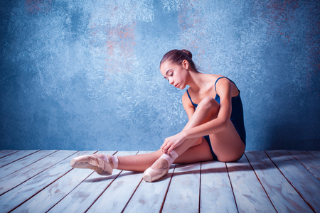 pointes: The  young ballerina  sitting on the wooden floor on blue background and  dressing pointes