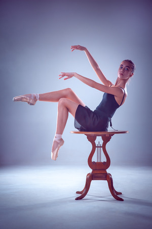 flexable: The silhouette of young ballerina on the wooden table on blue background
