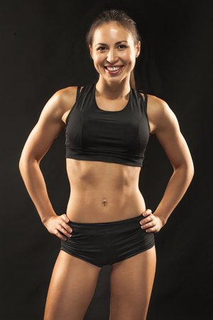 Muscular young woman athlete standing and looking in camera on black background.