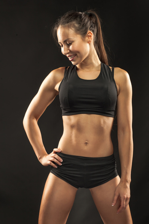 fitness abs female: Muscular young woman athlete standing and looking in camera on black background.
