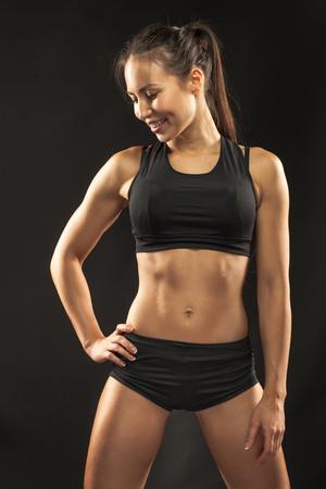 black girl: Muskul�sen jungen Frau Athlet Stehen und in der Kamera auf schwarzem Hintergrund. Lizenzfreie Bilder