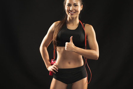one female: Muscular young woman athlete  with a skipping rope looking in camera on black background.