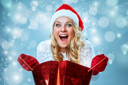 Beautiful young woman in Santa Claus clothes with a gift on a blue background