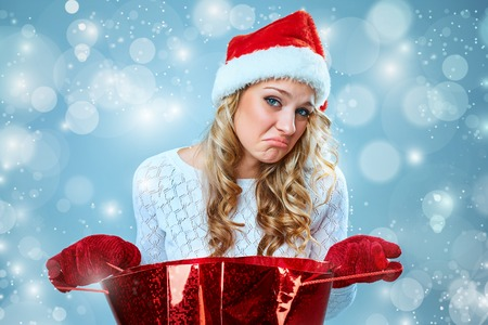 disenchantment: Frustrated and annoyed beautiful young woman in Santa Claus hat with a gift on a blue background