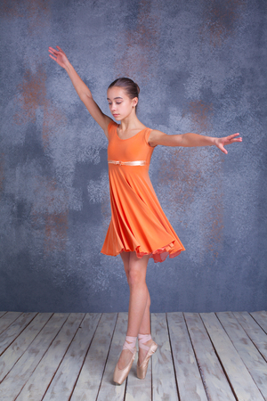 flexable: The  young ballerina  in orange dress  dancing in studio on gray background
