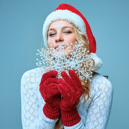 female christmas: Beautiful young woman in Santa Claus clothes with snowflakes on a blue background