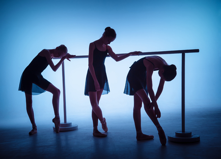 flexable: The silhouettes of young ballerinas stretching on the bar on blue background