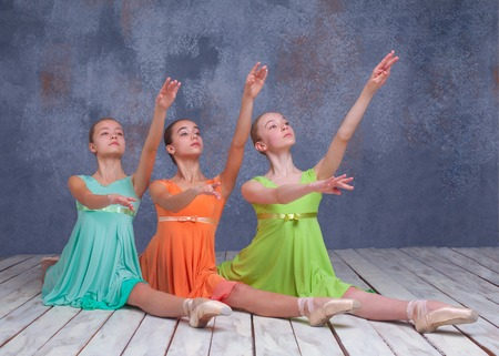 flexable: Three young ballerinas  posing on the floor on gray background