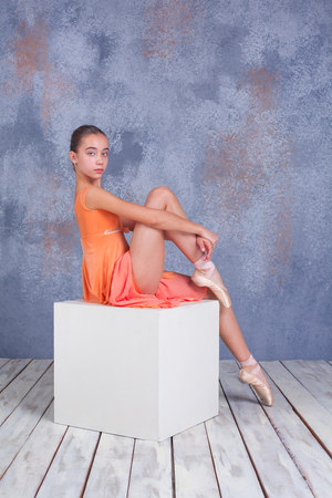 flexable: The  young ballerina  in orange dress  posing in studio on gray background