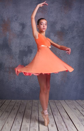 The  young ballerina  in orange dress  dancing in studio on gray background
