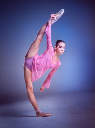 flexable: The  young ballerina  posing in studio on blue background  in stretching split Stock Photo