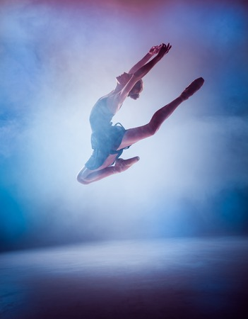 ballerina: The silhouette of young ballerina jumping on a blue  smoke background.