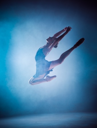 ballerina silhouette: The silhouette of young ballerina jumping on a blue  smoke background.