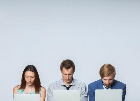 El equipo de negocios trabajando en las computadoras portátiles en la oficina en el fondo gris Foto de archivo