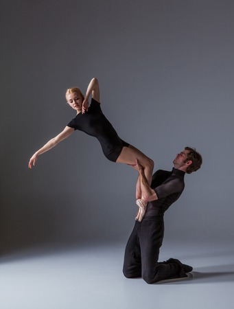 cool guy: The two young modern ballet dancers in black suits posing over gray studio background