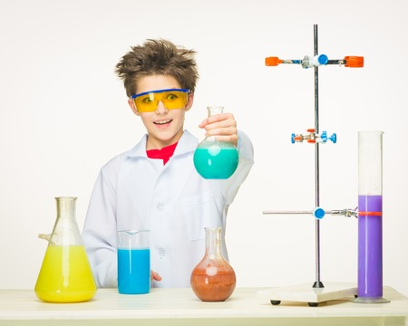 Little boy in a white coat as chemist doing experiment with multicolored chemical fluid in the laboratory on white background Stock Photo