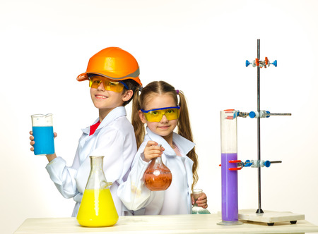 chemistry lesson: Two cute children at chemistry lesson making experiments on white background Stock Photo