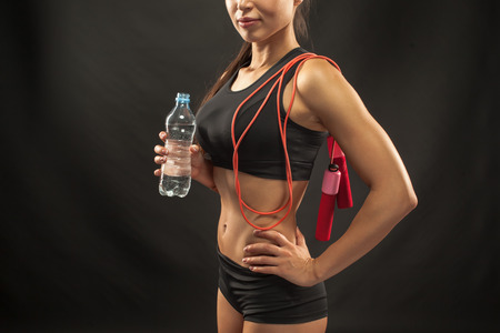 drinking water: Muscular young woman athlete  with a skipping rope drinking water on black background.