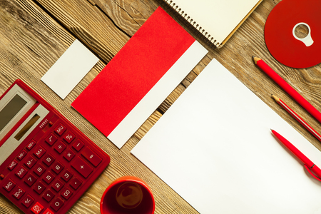 lapiz y papel: The mockup on wooden background with red calculator, pen, pencil, cup of coffee, white blank paper for writing, notebook and disk