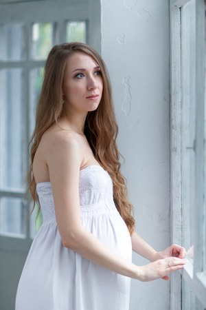 expectant arms: Portrait of the young pregnant woman in white dress standing against white home. Stock Photo