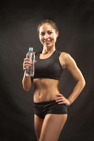 athletic body: Muscular young woman athlete drinking water on black background.