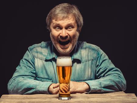éxtasis: Disfrutando de su cerveza favorita. La vista frontal del hombre sonriente guapo como ventilador en camisa de mezclilla con un vaso de cerveza, sentado en la mesa de madera. Concepto de entusiasmo y el éxtasis