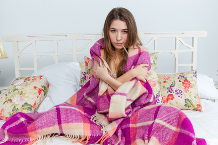 sick room: Young sick woman in blanket with  thermometer in bed at home