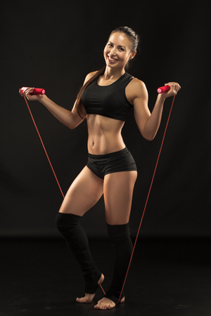 muscle girl: Muscular young woman athlete  with a skipping rope looking in camera on black background.