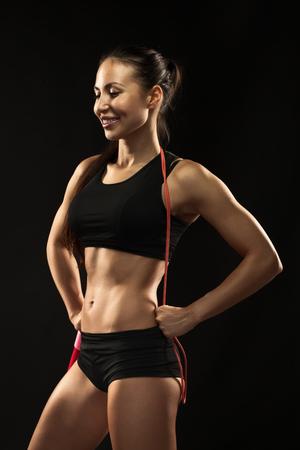 mooie vrouwen: Gespierde jonge vrouw atleet met touwtjespringen glimlachend op een zwarte achtergrond. Stockfoto