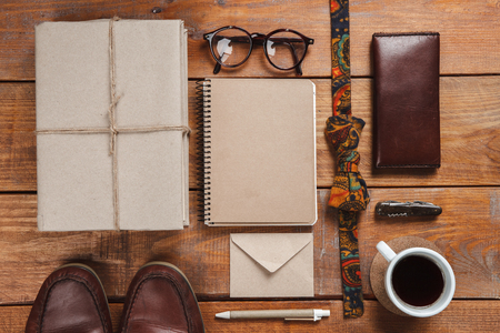 eather: Mens accessories - glasses, notebooks, pens, tie butterfly, partmane and leather shoes  on the wooden table