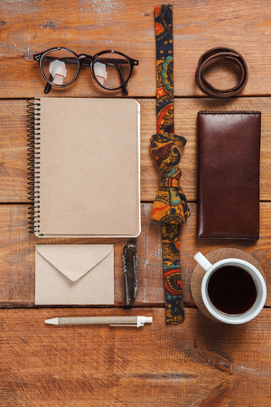 Mens accessories - glasses, notebooks, pens, tie butterfly, partmane and cup  on the wooden table