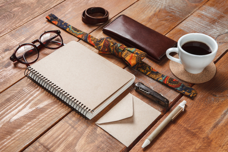 butterfly knife: Mens accessories - glasses, notebooks, pens, tie butterfly, partmane and cup  on the wooden table