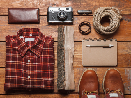 folding camera: Mens accessories -checkered shirt, notebooks, pens, retro camera, partmane and leather shoes  on the wooden table Stock Photo