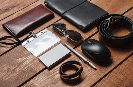 Men's accessories - sunglasses, partmane, pens, belt ,retro camera, badge on the wooden table