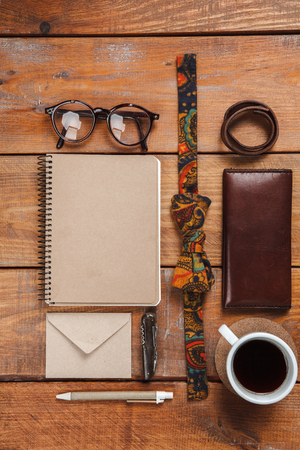 eather: Mens accessories - glasses, notebooks, pens, tie butterfly, partmane and cup  on the wooden table
