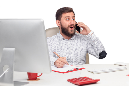 Portrait of surprised businessman sitting and talking on mobile phone in office