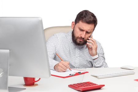 telephone salesman: Portrait of serious businessman, sitting and talking on mobile phone in office