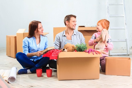 family moving house: The happy family  at repair and relocation. The family sitting  and geting things out of boxes against the new white apartment Stock Photo