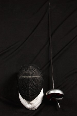 rapier: The fencing mask and rapier on on black fabric