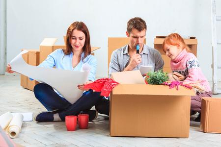 Die glückliche Familie zu Reparatur und Verlegung. Die Familienberatung zur Unterkunft auf einem Hintergrund von Boxen