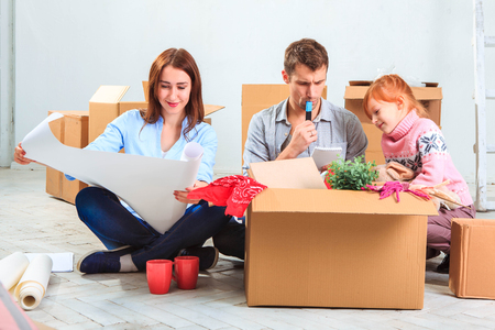people moving: The happy family  at repair and relocation. The family planing  to accommodation on a background of boxes