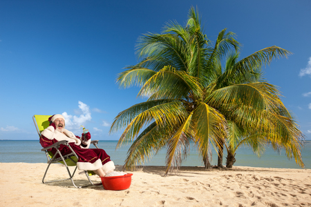beach happy new year: Santa Claus sitting in deck chair on the sunny beach  with blue sky and palm tree. Christmas Day concept. Stock Photo