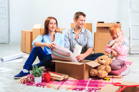 moving house: The happy family  at repair and relocation. The family planing  to accommodation on a background of boxes