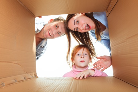 buyer: The smiling family in a cardboard box ready for moving house