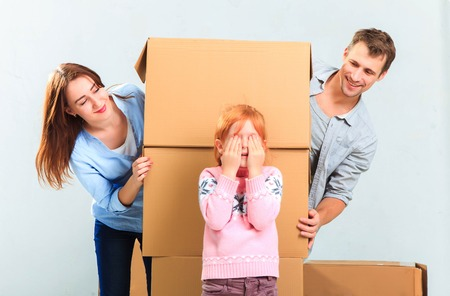 toy house: The happy family  at repair and relocation on a background of boxes