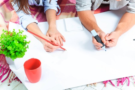 moving house: The hands of  family  at repair and relocation. The family planing  to accommodation on a floor Stock Photo