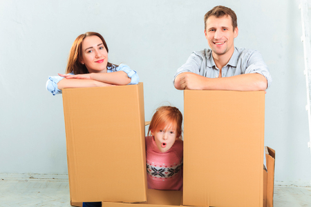 moving house: The happy family  at repair and relocation on a background of boxes